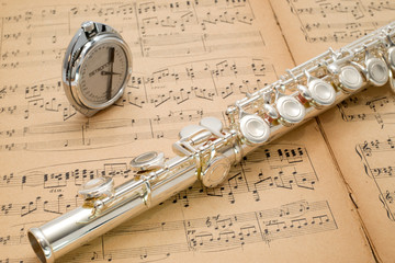 Silver flute and pocket metronome  on an ancient music score