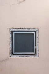 square window on beige wall
