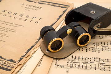 Opera glasses with case on an ancient music score background