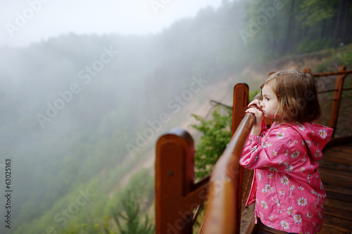 Adorable little enjoing the view on rainy day