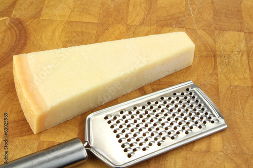 Parmesan cheese and grater on kitchen board.