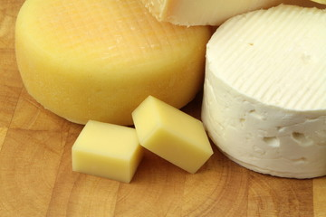 Various cheeses on wood background