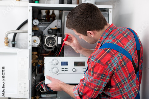 Technician servicing heating boiler - 63027789