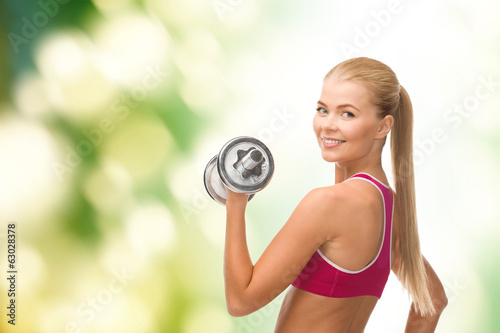 smiling woman with heavy steel dumbbell