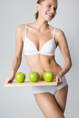 young slim girl holding a green apple