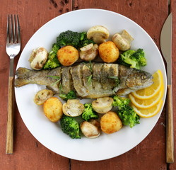 roasted trout fish with vegetables and lemon on a plate