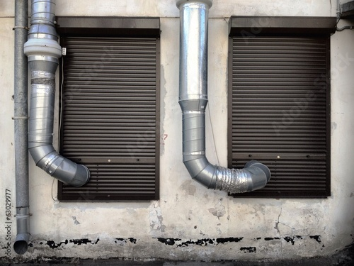 pipes and rain gutter on weathered wall
