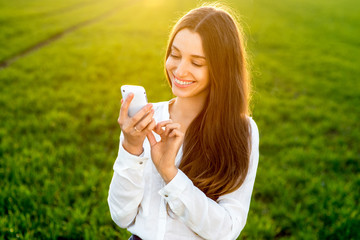 Young woman laughing and typing message in smart phone in the gr