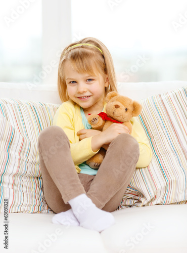 smiling girl with teddy bear sitting on sofa