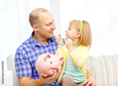 happy father and daughter with big piggy bank
