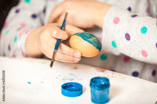 Closeup shot of girl holding brush and painting ester egg