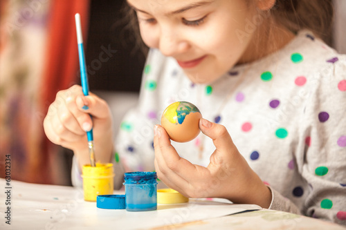 Happy little girl painting easter egg