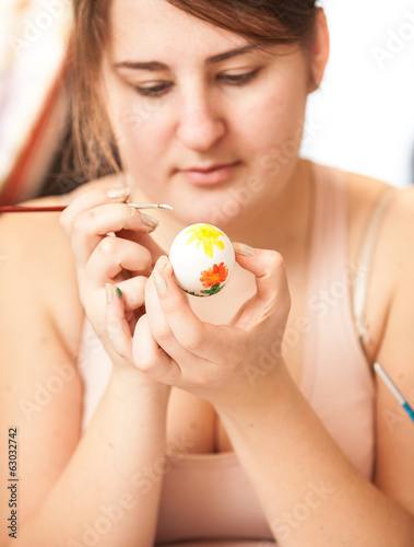 brunette woman painting white easter egg