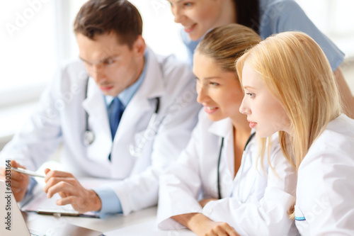 group of doctors looking at laptop computer
