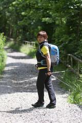 Frau mit Wanderstöcken auf einem Waldweg