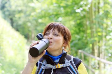 Wanderin trinkt aus einer Trinkflasche