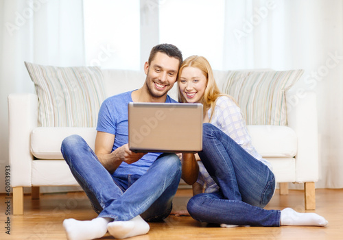smiling happy couple with laptop at home