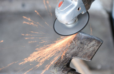 Close up of a man sharpen an ax using electric grinder. Sparks w