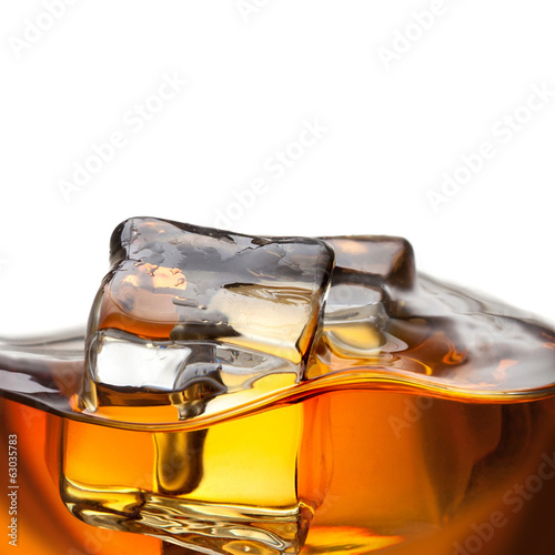 Close up splash of whiskey with ice isolated on white