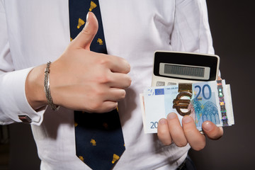 Businessman in nice suit showing OK. Money and calculator in his