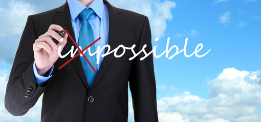 Businessman turning word impossible into possible