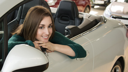 Young woman holding car key inside car dealership