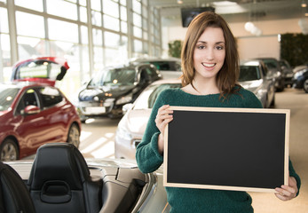 Young woman holding blackboard inside car dealership