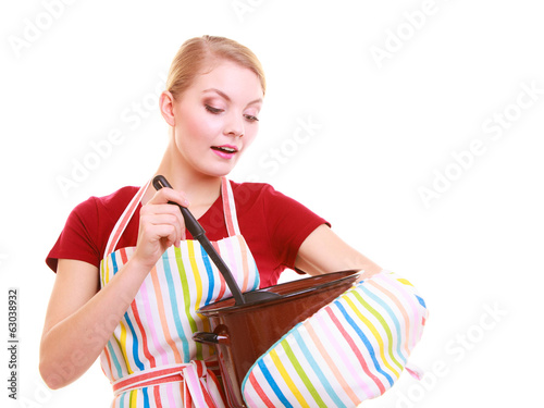 Happy housewife or chef in kitchen apron with pot of soup ladle