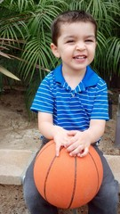 Cute mixed-race boy smiles as he waits to play basketball.