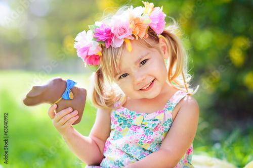 Leinwanddruck Bild cute easter girl with chocolate bunny
