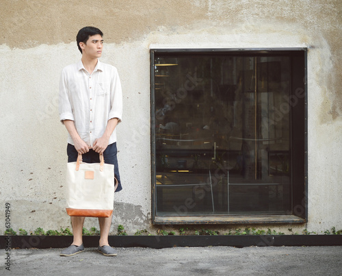 Attractive man with canvas bag on grunge concrete wall