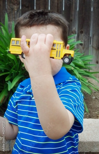 Young boy playing with a miniature schoolbus toy outside.