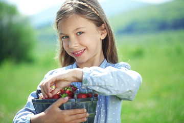 Child eating strawberries in a field