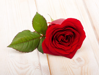 Single red rose flower with leaf on wooden background