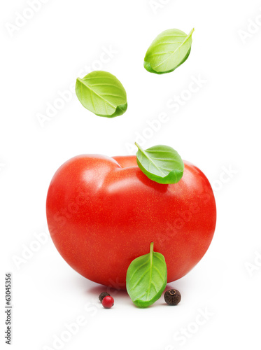 Red tomato and basil leaves spice falling down isolated on white
