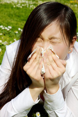 Sick chinese woman sneezing because of allergy and flu
