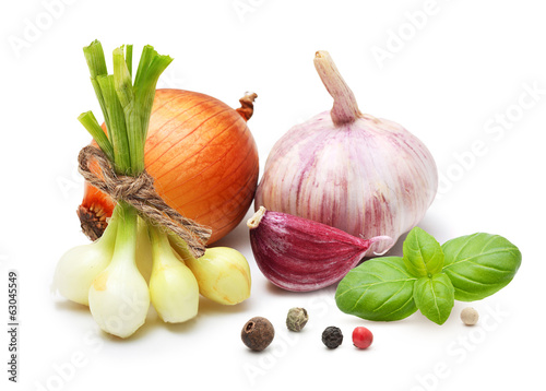 Garlic clove, onion and spices on wooden background