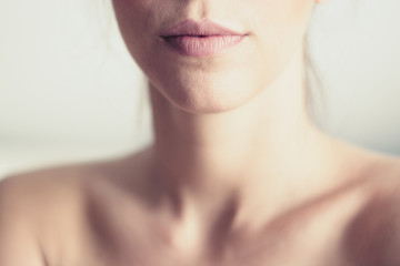 Closeup of young woman's pink lips and neck