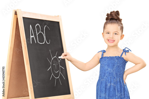 Girl writing on a blackboard with chalk