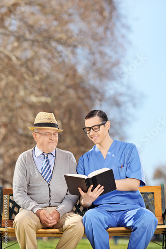 Male nurse reading to a pensioner in park