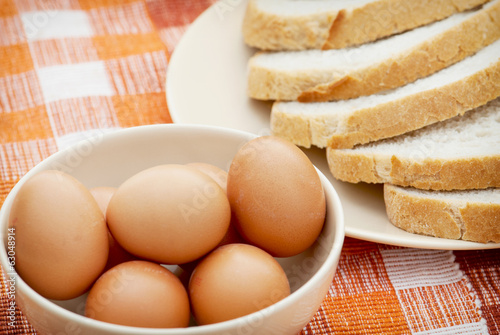 Raw eggs and sliced of wheat bread