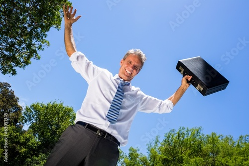 Happy businessman carrying briefcase against sky