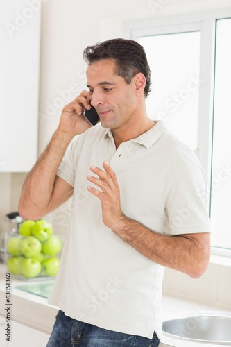Handsome man using mobile phone in kitchen