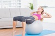 Smiling blonde doing sit ups with exercise ball