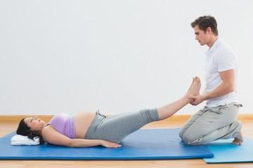 Masseur lifting pregnant womans legs on blue mat