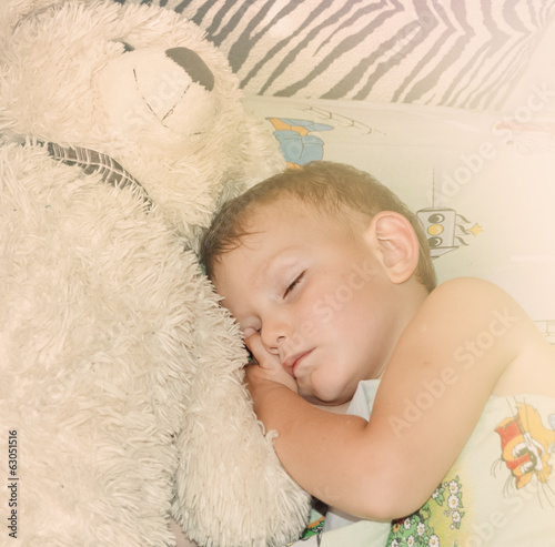 Cute little boy sleeping with his teddy bear