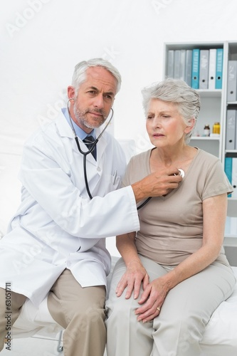 Doctor checking patients heartbeat using stethoscope