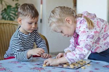 Young girl and boy playing checkers together