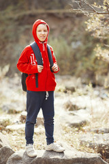 Happy smiling hiker boy with backpack in forest. Dressed in red