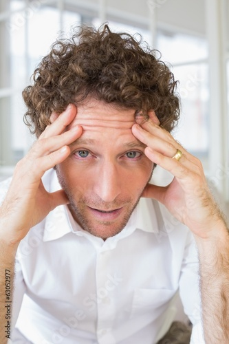 Worried man sitting with head in hands at home